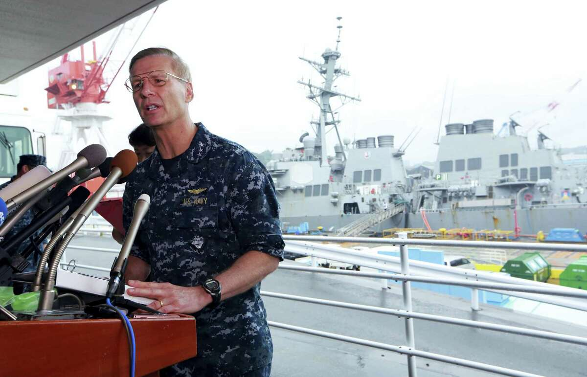 Vice Adm. Joseph Aucoin, Commander of the U.S. 7th Fleet, speaks during a press conference on the status of USS Fitzgerald, seen at the rear, and search and rescue efforts for seven missing Fitzgerald crew members at the U.S. Naval base in Yokosuka, southwest of Tokyo Sunday.