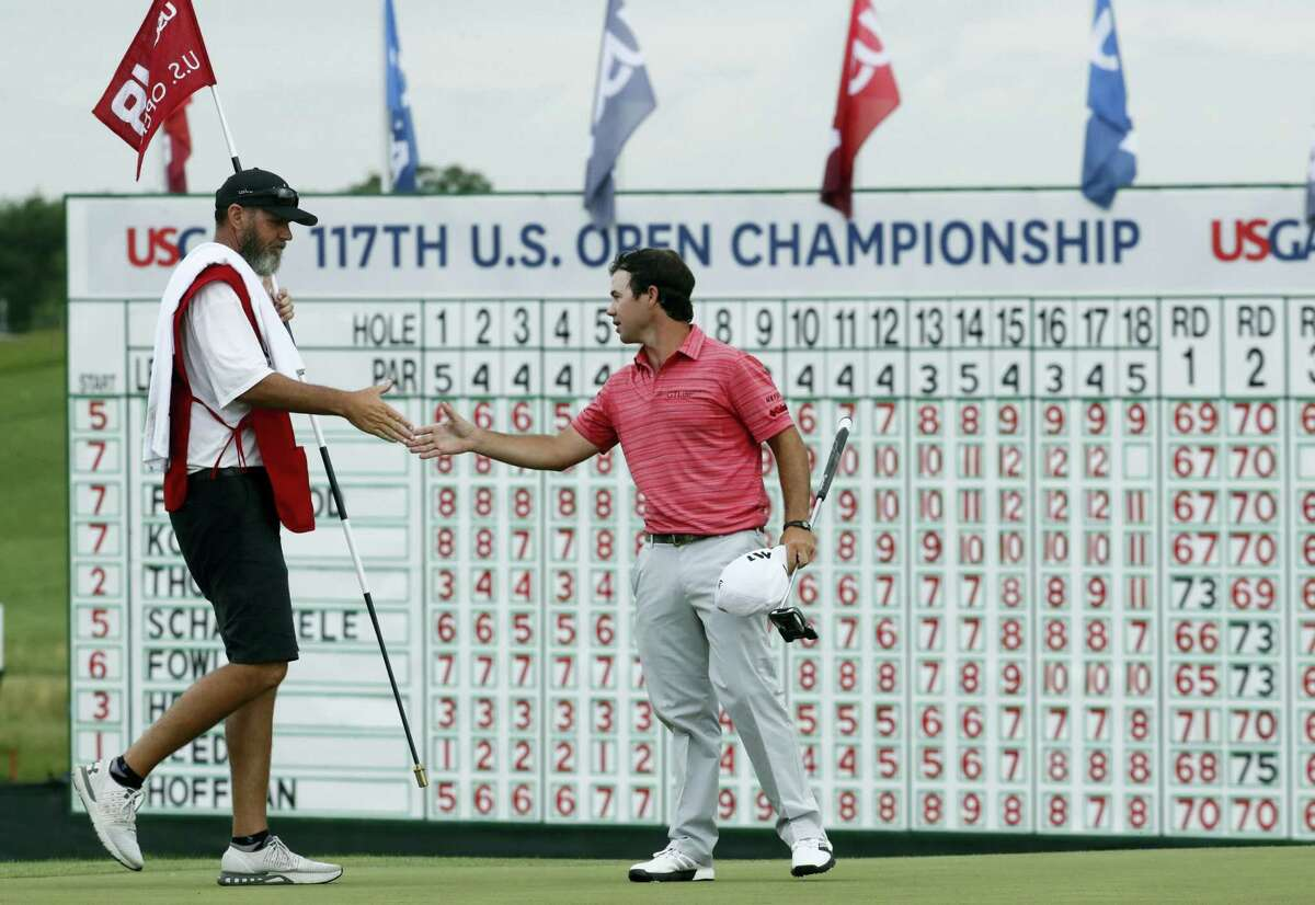 Brian Harman shakes hands with his caddie after the third round.