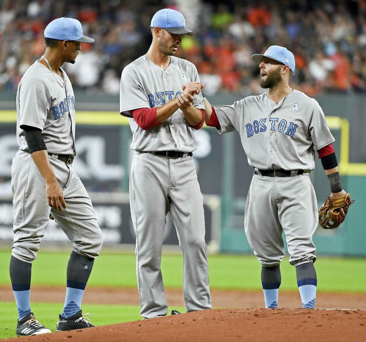 Red Sox second baseman Dustin Pedroia, right, talks with starting pitcher Rick Porcello, center, as shortstop Xander Bogaerts looks on during Saturday's game in Houston.