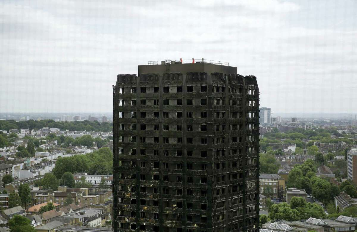 Emergency workers walk on the roof of the fire-gutted Grenfell Tower in London, Friday, June 16, 2017, after a fire engulfed the 24-storey building on Wednesday morning. Grief over a high-rise tower blaze that killed dozens of people turned to outrage Friday amid suggestions that materials used in a recent renovation project may have contributed to the disaster.