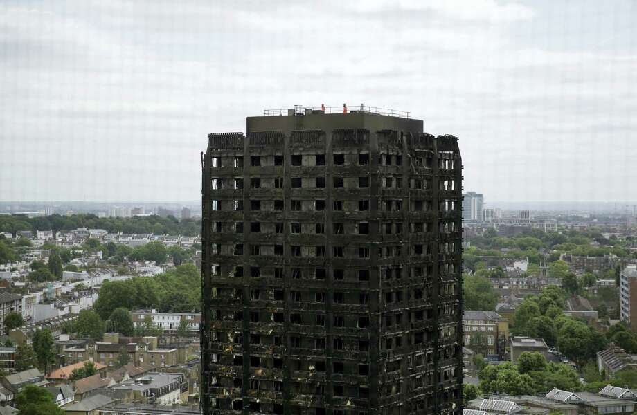 Emergency workers walk on the roof of the fire-gutted Grenfell Tower in London, Friday, June 16, 2017, after a fire engulfed the 24-storey building on Wednesday morning. Grief over a high-rise tower blaze that killed dozens of people turned to outrage Friday amid suggestions that materials used in a recent renovation project may have contributed to the disaster. Photo: AP Photo/Matt Dunham   / Copyright 2017 The Associated Press. All rights reserved.