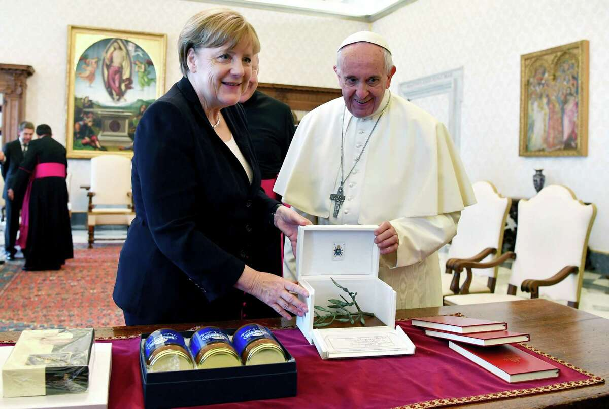 Pope Francis and German Chancellor Angela Merkel exchange gifts on the occasion of their private audience, at the Vatican, Saturday, June 17, 2017.