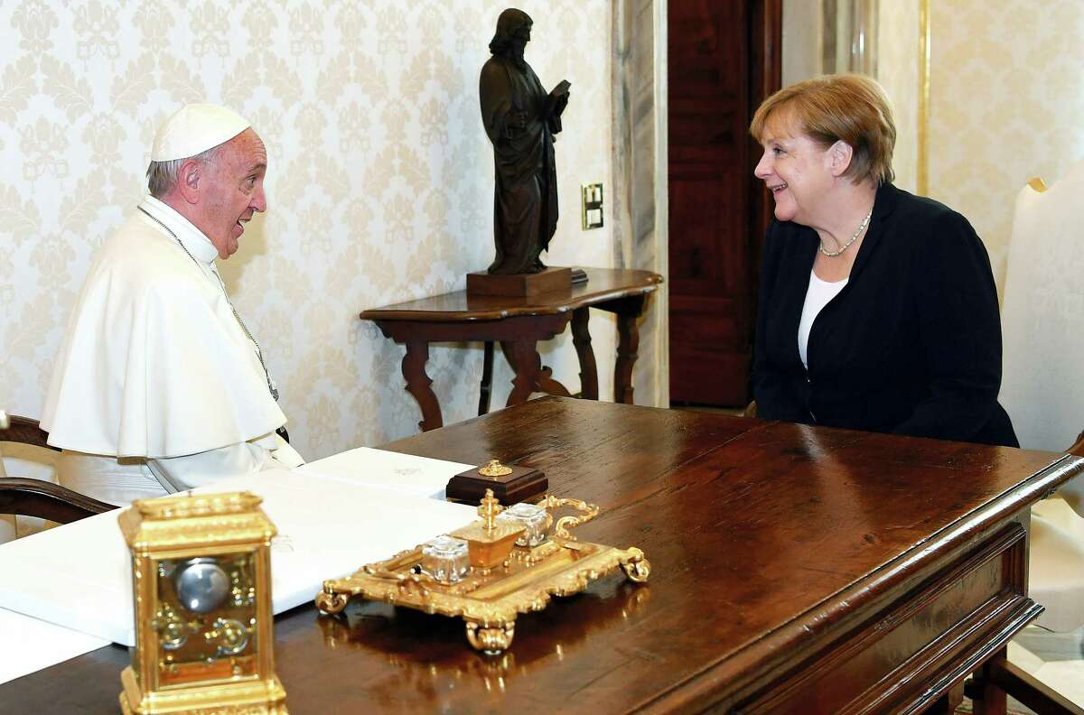 Pope Francis sits at a table with German Chancellor Angela Merkel on the occasion of their private audience, at the Vatican City, Saturday, June 17, 2017.