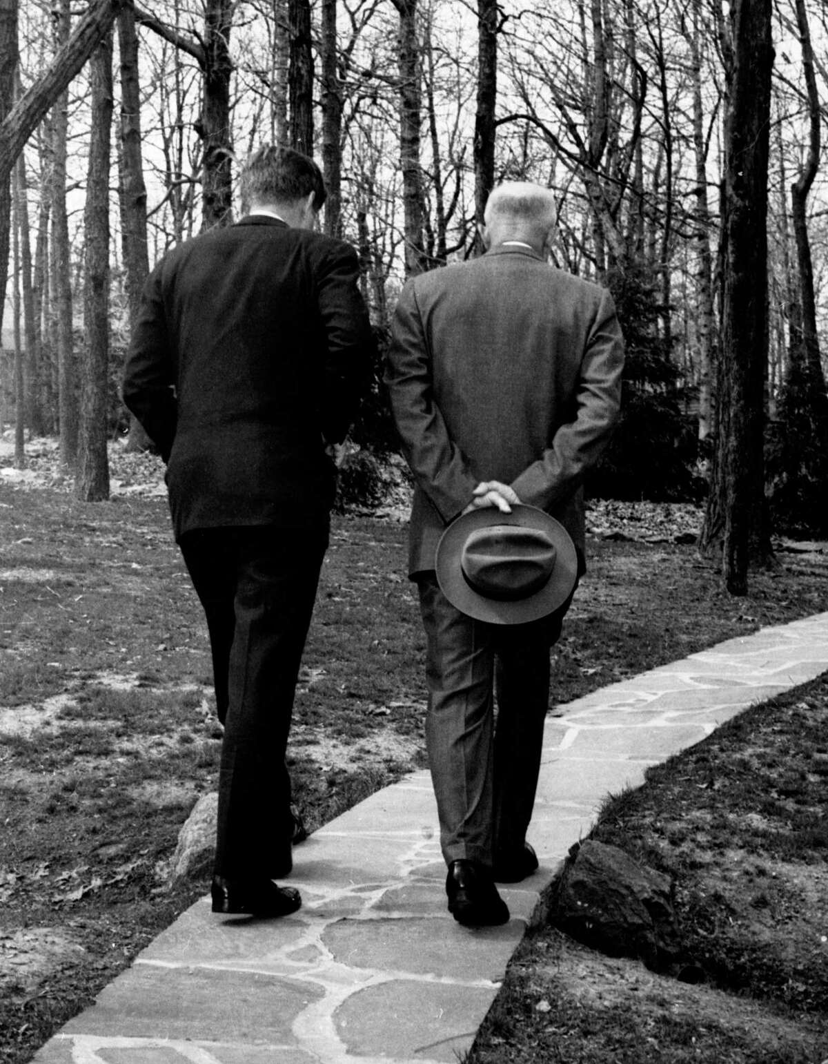 President John F. Kennedy, left, and former President Dwight D. Eisenhower with their heads bowed as they walk along a path at Camp David in Thurmond, Md.