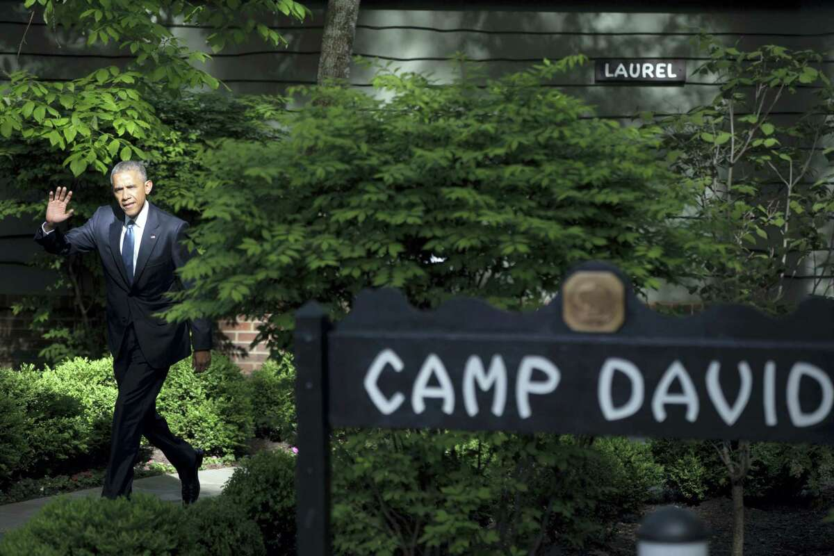 FILE - In this May 14, 2015, file photo, President Barack Obama waves to members of the media after meeting with Gulf Cooperation Council leaders and delegations at Camp David, Md. President Donald Trump is picking simple over swanky this weekend. Nearly five months into his presidency, Trump is heading to Camp David, the government-owned retreat in Maryland's Catoctin Mountains, for the first time. A frequent weekend traveler, Trump has so far favored his palatial residences in Florida and New Jersey over the wooded hideaway used by many presidents for a break from Washington.