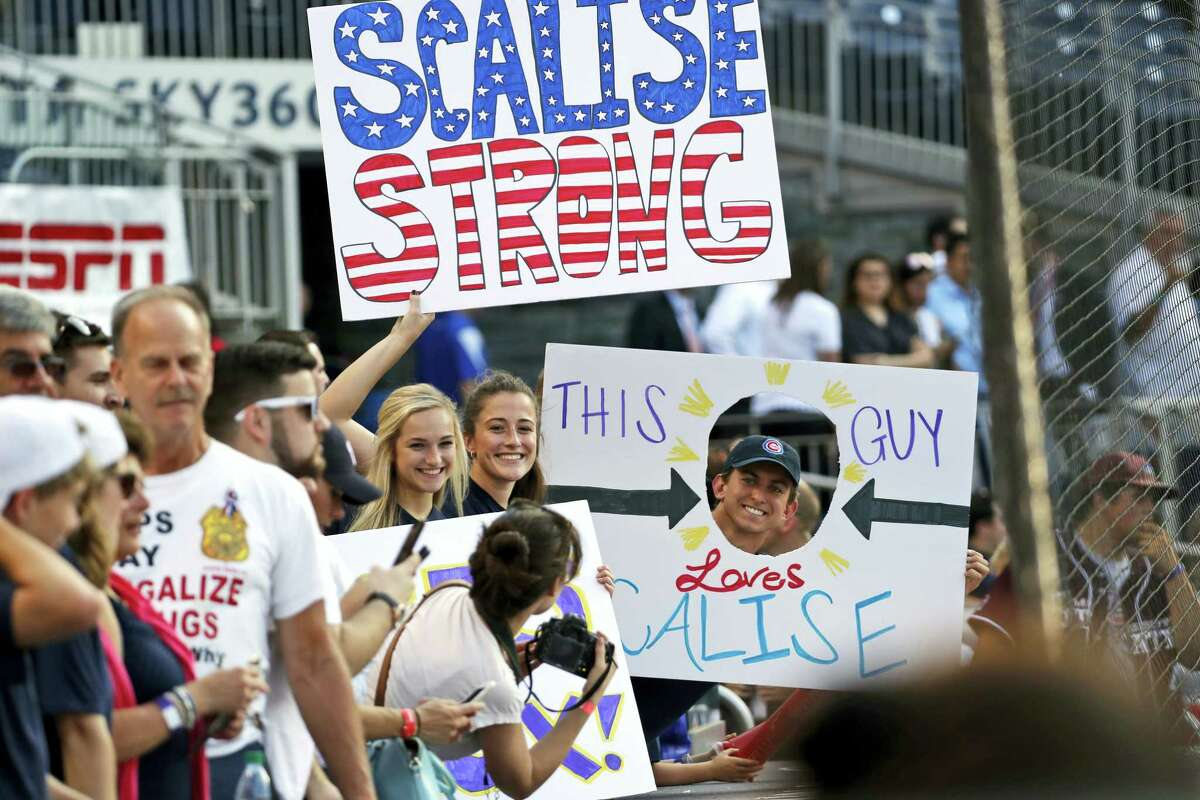 Supporters of House Majority Whip Steve Scalise, R-La., hold signs before the Congressional baseball game.