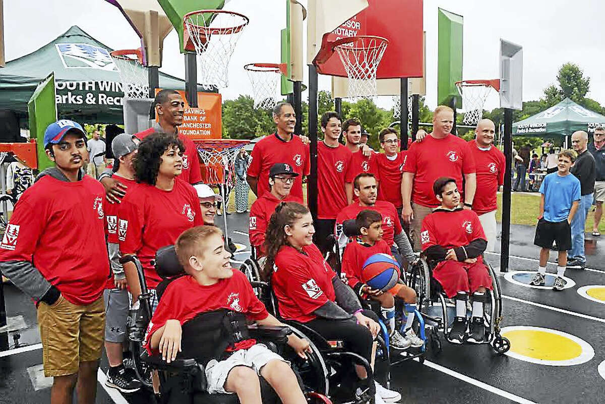 UConn coach Kevin Ollie, the South Windsor unified sports team and the Ryan Martin Wheelchair Basketball team celebrate the opening of Kevin's Kourt in South Windsor on Friday.