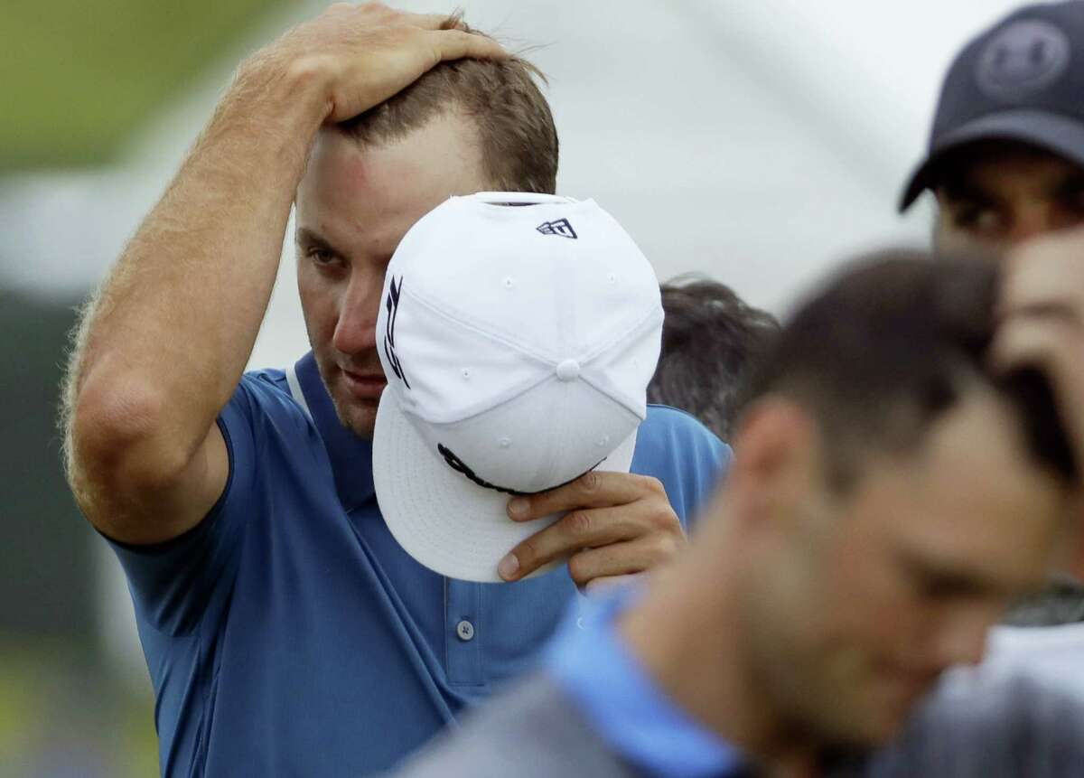Dustin Johnson wipes his head as he walks off the 18th green on Friday. Johnson missed the cut.