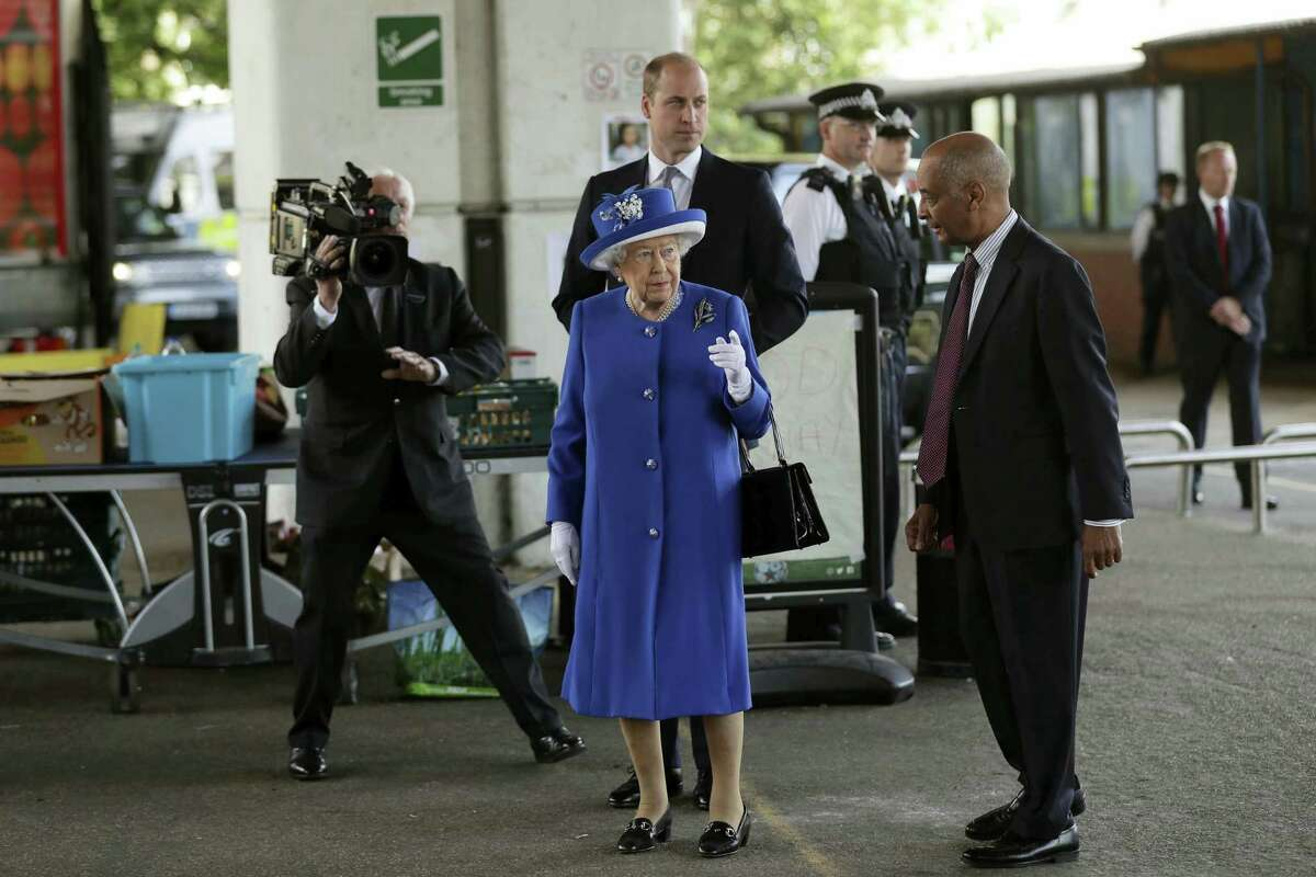 Britain's Queen Elizabeth II and William the Duke of Cambridge, centre rear, look towards Grenfell Tower as they visit the the Westway sports centre which is providing temporary shelter for those who have been made homeless in the fire disaster in London, Friday, June 16, 2017. Relatives of those missing after a high-rise tower blaze in London are searching frantically for their loved ones, as the police commander in charge of the investigation says he hopes the death toll will not rise to three figures.
