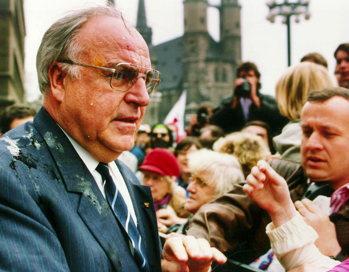 In this May 10, 1991 file photo German Chancellor Helmut Kohl looks dismayed when he was hit by eggs in Halle, eastern Germany. Demonstrators threw eggs and color bags to the Chancellor when he was entering the city hall. Kohl visited the industrial region of Halle in former East Germany where many people are unemployed. Kohl died June 16, 2017.