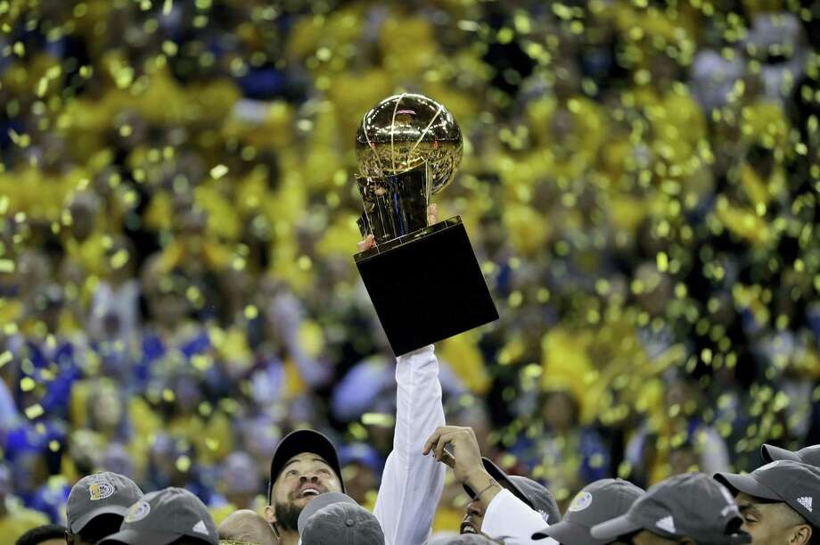 Golden State Warriors center JaVale McGee holds up the Larry O'Brien NBA Championship Trophy after Game 5 of basketball's NBA Finals between the Warriors and the Cleveland Cavaliers in Oakland, Calif. on June 12, 2017. The Warriors won 129-120 to win the NBA championship. Photo: AP Photo — Marcio Jose Sanchez  / Copyright 2017 The Associated Press. All rights reserved.
