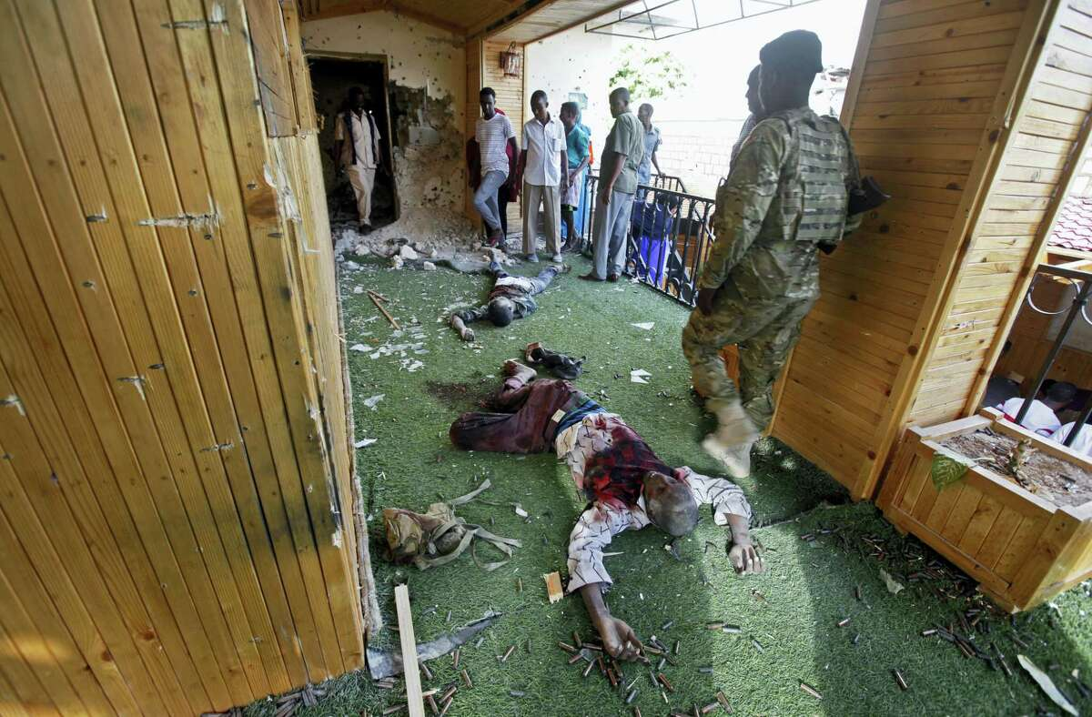 """Somali soldiers and others stand near the bodies of some of the al-Shabab attackers at the scene of a car bomb blast and gun battle targeting a restaurant in Mogadishu, Somalia Thursday, June 15, 2017. Somalia's security forces early Thursday morning ended a night-long siege by al-Shabab Islamic extremists at the popular """"Pizza House"""" restaurant in the capital."""