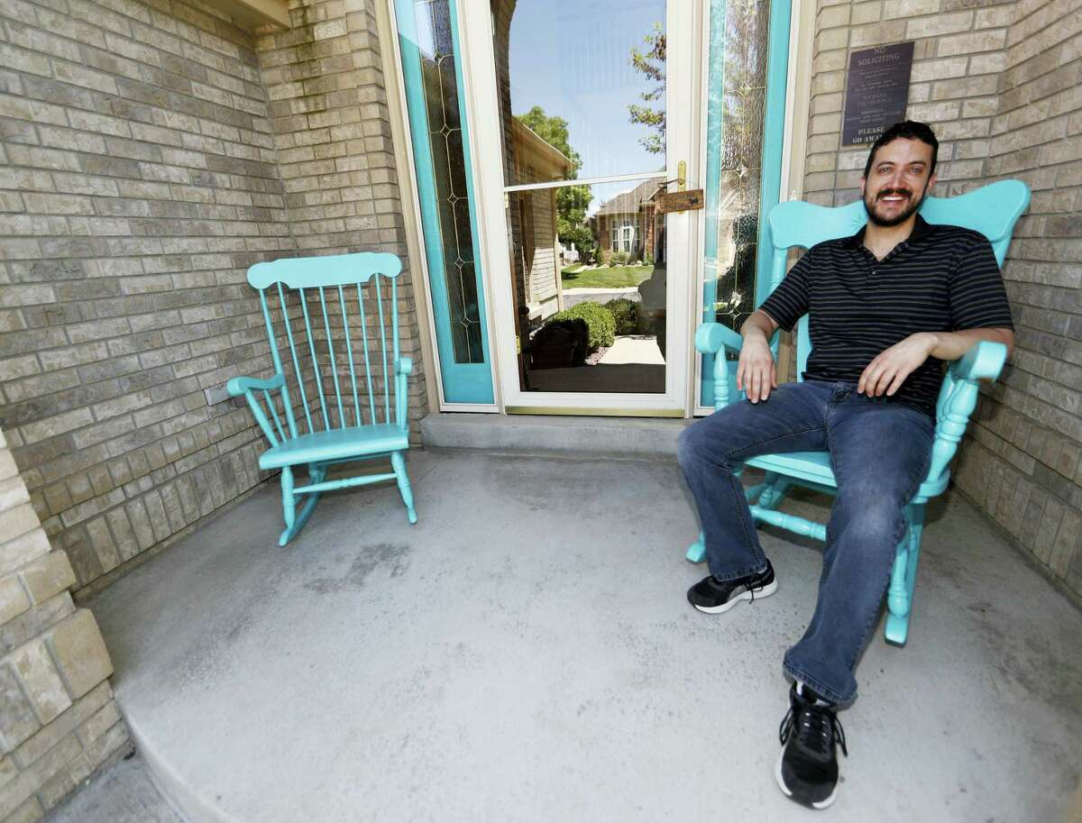 Danny Aguilar takes a seat in one of the rocking chair on the front porch of his home in Lakewood, Colo. Aguilar, like nearly half of Americans surveyed in a new poll conducted by The Associated Press-NORC Center Public Affairs Research, said they will not be taking a vacation this summer because they can not afford it or can not get time away from the job.