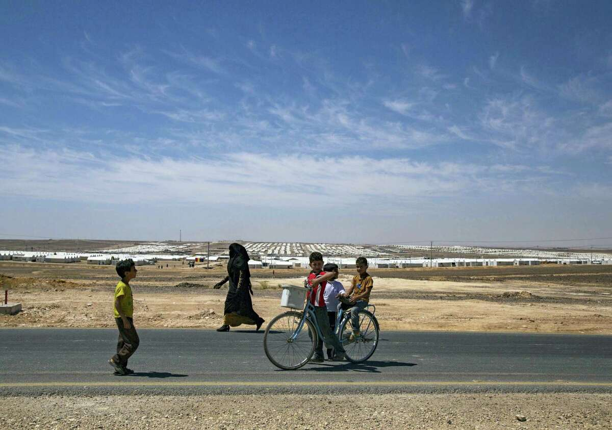 Syrian refugees walk near the Azraq Refugee Camp where the U.N. refugee agency inaugurated a solar power plant, in Jordan's northern desert.