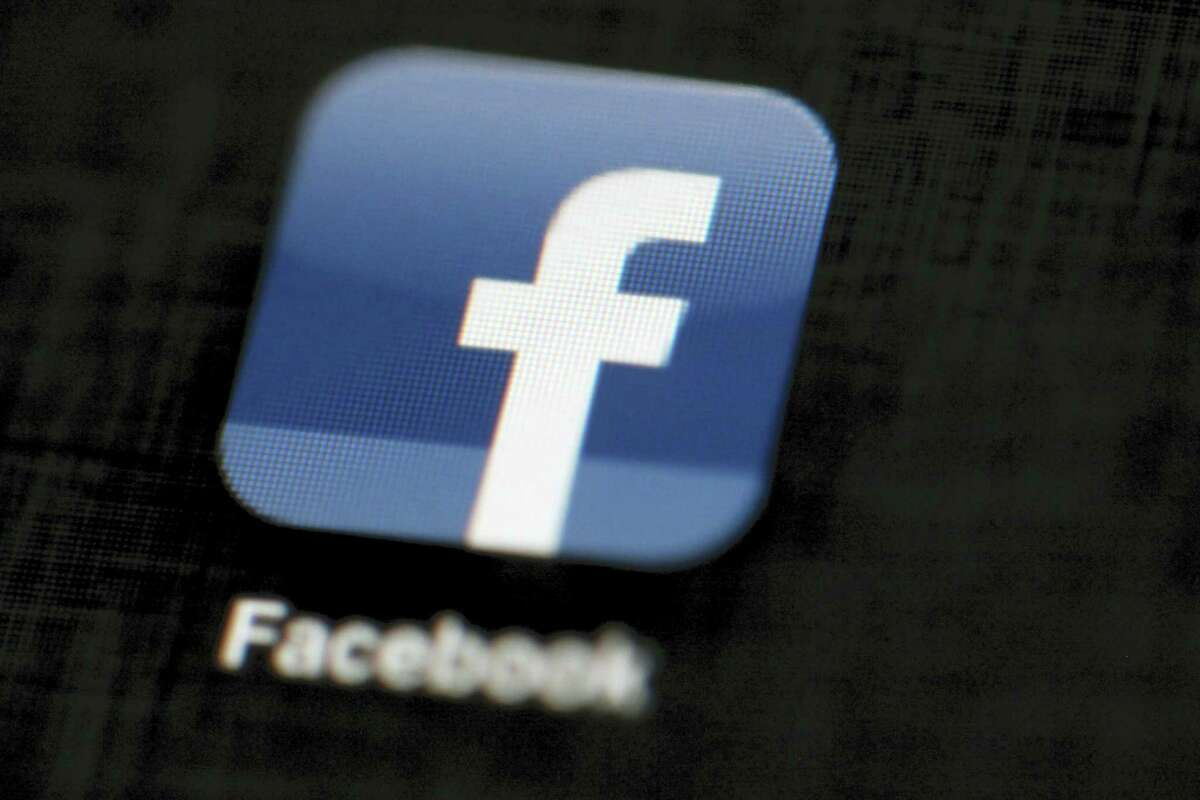 In this May 16, 2012, file photo, the Facebook logo is displayed on an iPad in Philadelphia. On Thursday, June 15, 2017, Facebook said it's using artificial intelligence to help it combat terrorists' use of its platform. The company's announcement comes as it faces growing pressure from government leaders to identify and prevent the spread of content from terrorist groups on its massive social network.