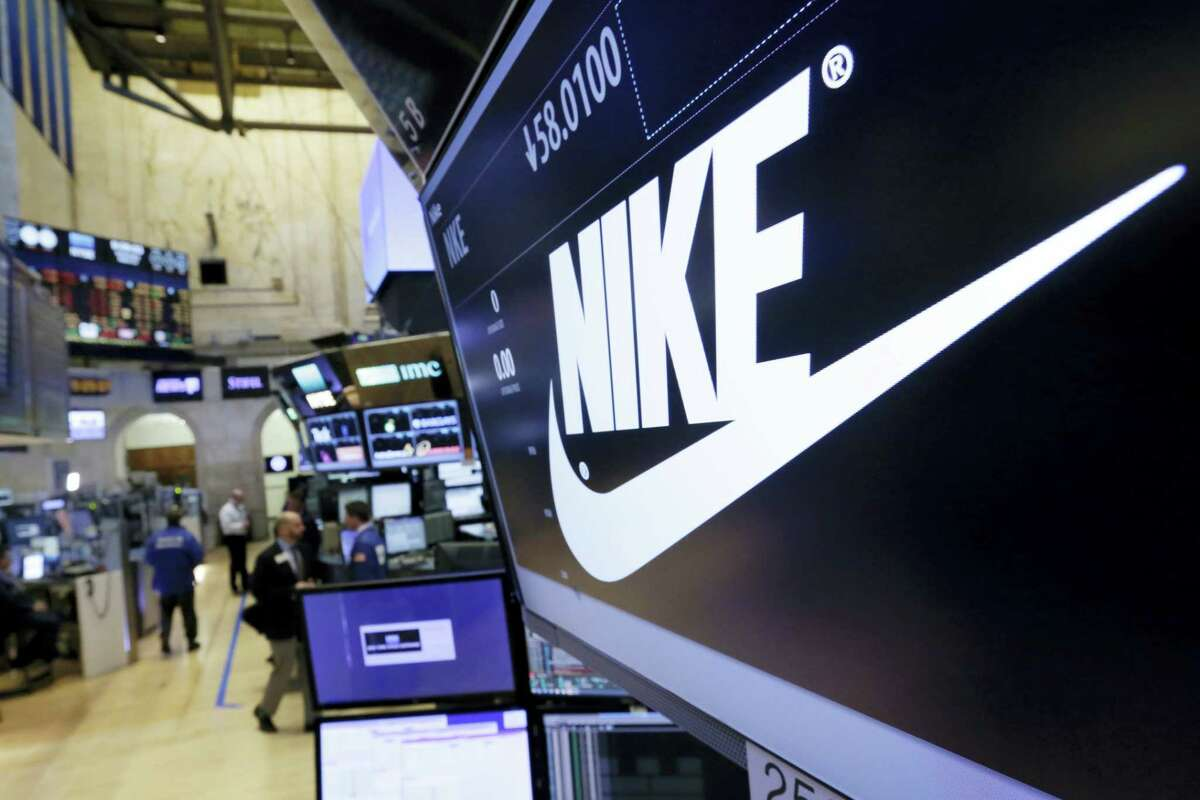 The Nike logo appears above the post where it trades on the floor of the New York Stock Exchange.