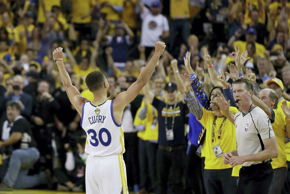 Golden State Warriors guard Stephen Curry (30) celebrates with fans after Game 5 of basketball's NBA Finals between the Warriors and the Cleveland Cavaliers in Oakland, Calif., on Monday. The Warriors won 129-120 to win the NBA championship.