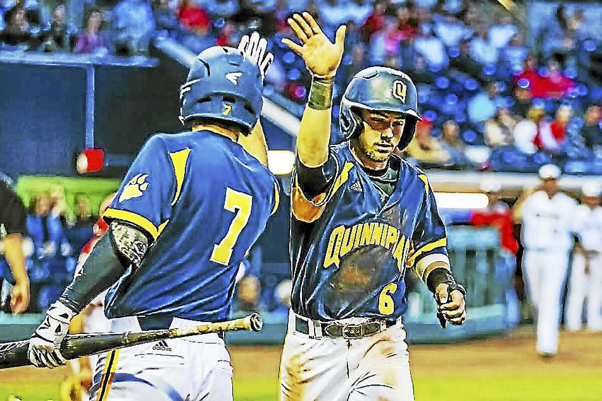 Quinnipiac's Matt Batten (right, No. 6) is congratulated by teammate Brian Moskey after scoring a run in Bobcats' game against Hartford at Dunkin' Donuts Park on April 11.