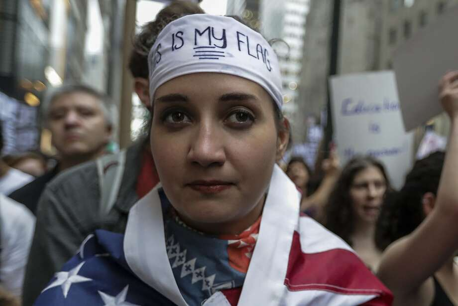 "A demonstrator wears an American flag during the ""Defend DACA & TPS"" rally outside of Trump Tower in New York on Aug. 15. Photo: Jeenah Moon, Bloomberg"