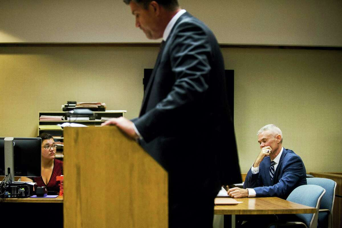 Special Agent Jeff Seipenko, center, listens as Genesee District Judge David Guinn authorizes charges Wednesday, June 14, 2017, in Flint, Mich., for Department of Health and Human Services Director Nick Lyon and Chief Medical Executive Dr. Eden Wells in relation to the Flint water crisis. Lyon is accused of failing to alert the public about an outbreak of Legionnaires' disease in the Flint area, which has been linked by some experts to poor water quality in 2014-15. Wells was charged with obstruction of justice and lying to a police officer.