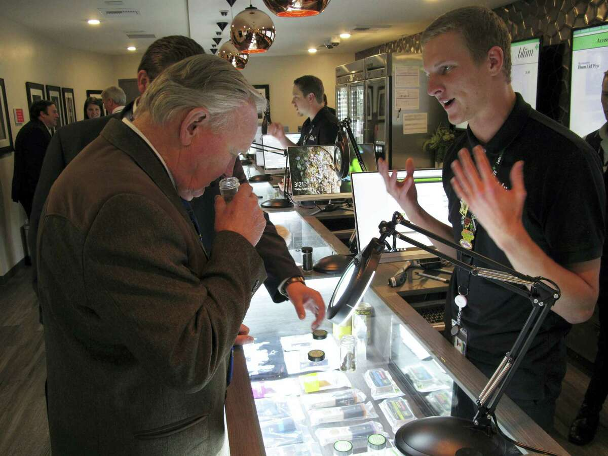 In this March 24, 2017 photo, Nevada state Sen. Don Gustavson, R-Sparks, smells a sample of marijuana as Christopher Price, a ''budtender'' at the Blum medical marijuana dispensary, describes the operation during a brief tour a the store in Reno, Nev. A judge in Nevada is trying to decide whether the state's first sales of recreational marijuana should begin as scheduled July 1 despite complaints from alcohol distributors. Lawyers for the liquor distributors and the Nevada Department of Taxation go before Judge James Wilson in Carson City on June 13, 2017 to argue the case.