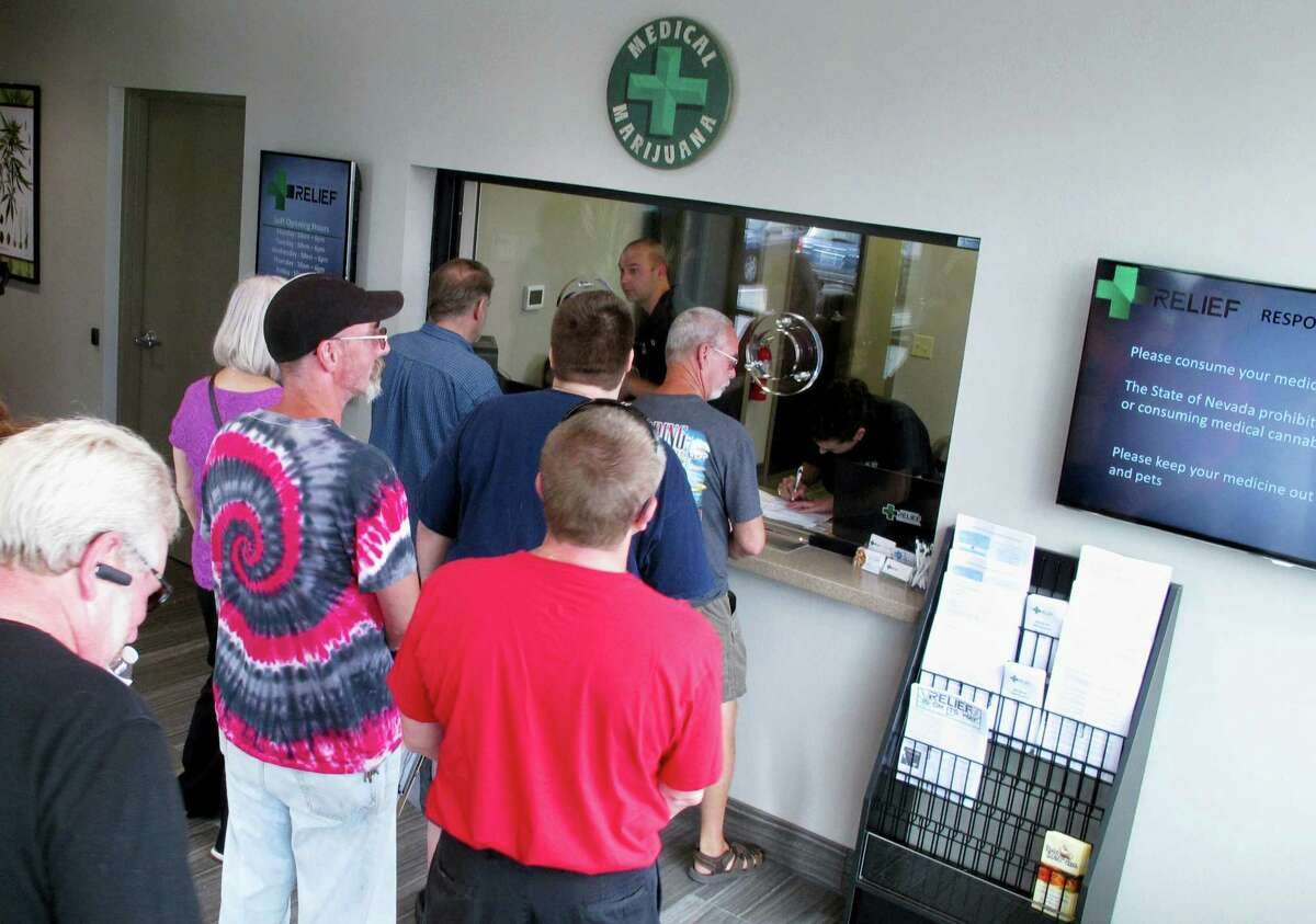 In this July 31, 2015 photo, people line up to be among the first in Nevada to legally purchase medical marijuana at the Silver State Relief dispensary in Sparks, Nev. A judge in Nevada is trying to decide whether the state's first sales of recreational marijuana should begin as scheduled July 1 despite complaints from alcohol distributors. Lawyers for the liquor distributors and the Nevada Department of Taxation go before Judge James Wilson in Carson City on June 13, 2017 to argue the case.
