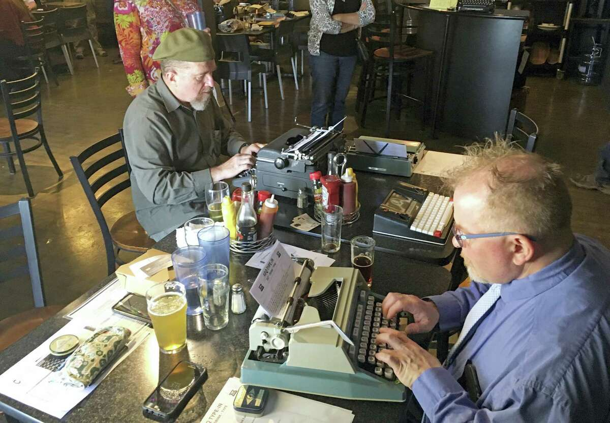 """In this April 23, 2017 photo, Joe Van Cleave, left, and Rich Boucher, right, try out various vintage typewriters at a """"type-in"""" in Albuquerque, N.M. """"Type-ins"""" are social gatherings in public places where typewriter fans test different vintage machines. The vintage typewriter is making a comeback with a new generation of fans gravitating to machines that once gathered dust in attics and basements across the country."""