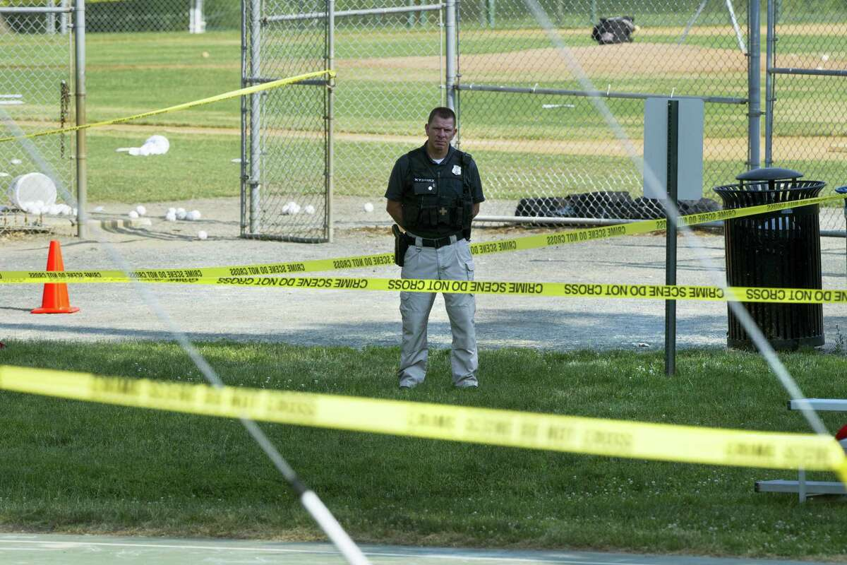 A police officer stands watch behind police tape near strewn baseballs on a field in Alexandria, Va., Wednesday, after a multiple shooting involving House Majority Whip Steve Scalise of La.