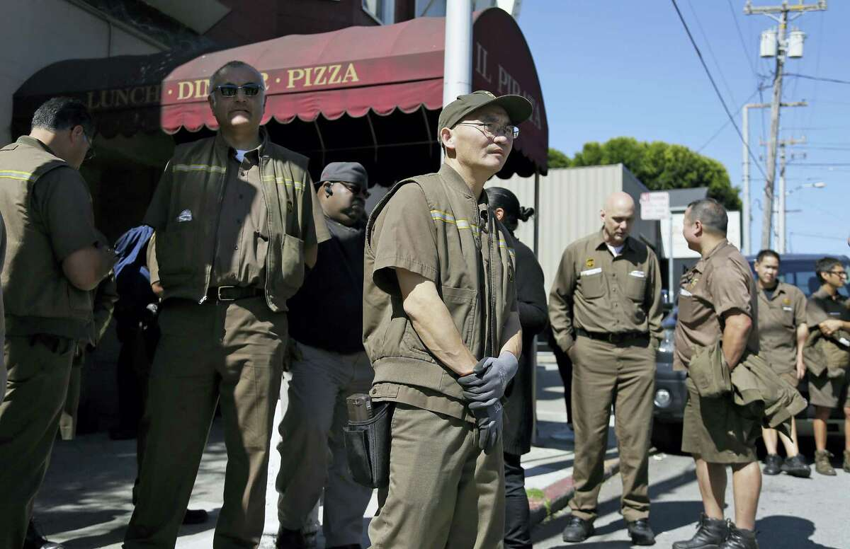 UPS workers gather outside a UPS package delivery warehouse where a shooting took place Wednesday, June 14, 2017, in San Francisco. A UPS spokesman says four people were injured in the shooting at the facility and that the shooter was an employee. (AP Photo/Eric Risberg)