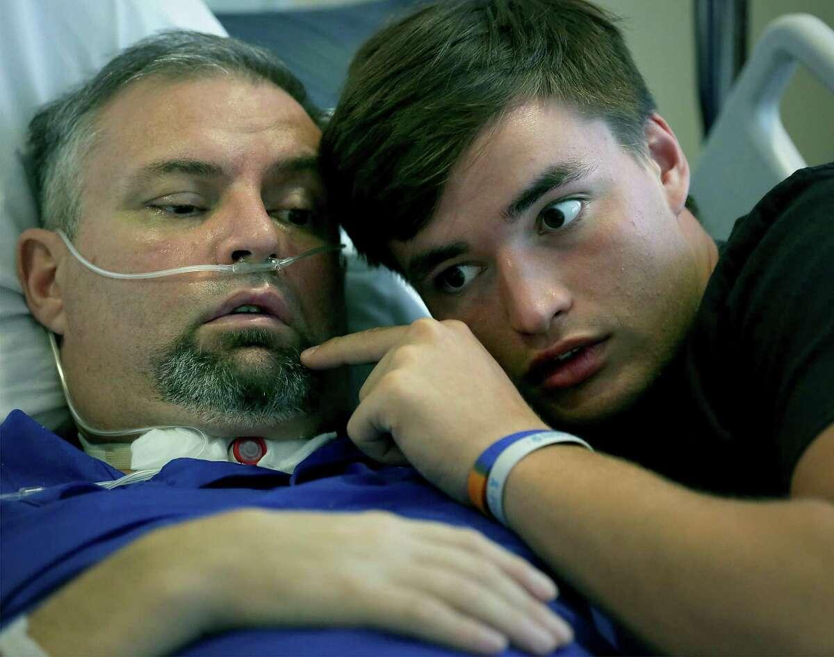 The family of Johan Dinkelmann gather around him at Select Rehabilitation Hospital of San Antonio on Aug. 14, 2017. Zadock Dinkelmann (right), Somerset's quarterback, communicates with his father.