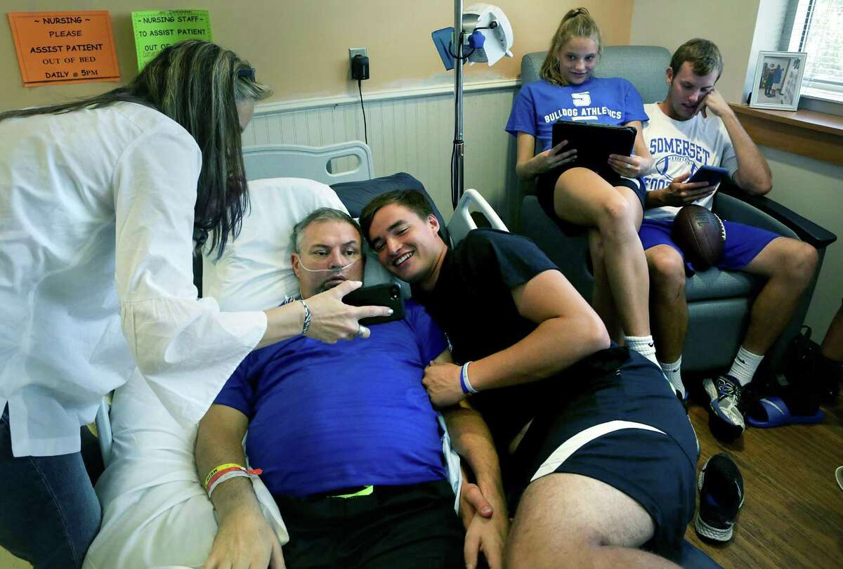 The family of Johan Dinkelmann, Somerset H.S. Athletic Director and football defensive coordinator, gather around him at Select Rehabilitation Hospital of San Antonio on Monday, Aug. 14, 2017. Dinkelmann suffered a series of strokes while attending a track meet in April. Johan's son Zadock Dinkelmann, lying next to his father, poses for a photo taken by Dee Dinkelmann, left, Johan's wife. Taylor Dinkelmann and her brother Stevie Dorman, right, check their electronic devises.