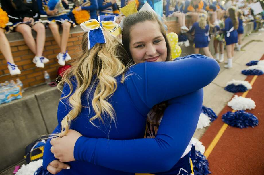 Midland senior Dezirae Rupert, right, hugs a fellow cheerleader after a ceremony celebrating the squad's seniors before Midland High School's season-opening football game against Traverse City West on Thursday, August 24, 2017 at Midland Community Stadium. Photo: (Katy Kildee/kkildee@mdn.net)