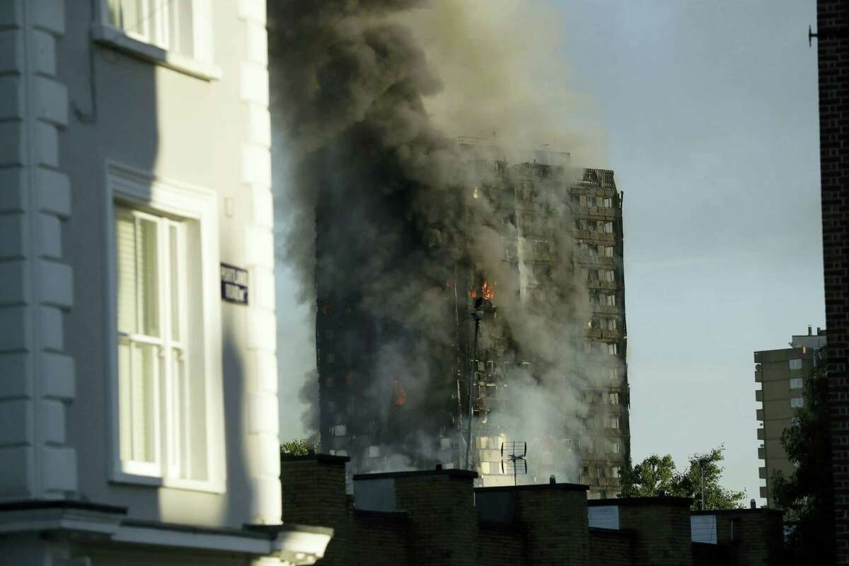 Smoke rises from a building on fire in London on June 14, 2017. A massive fire raced through the 27-story high-rise apartment building in west London early Wednesday, sending at least 30 people to hospitals, emergency officials said.