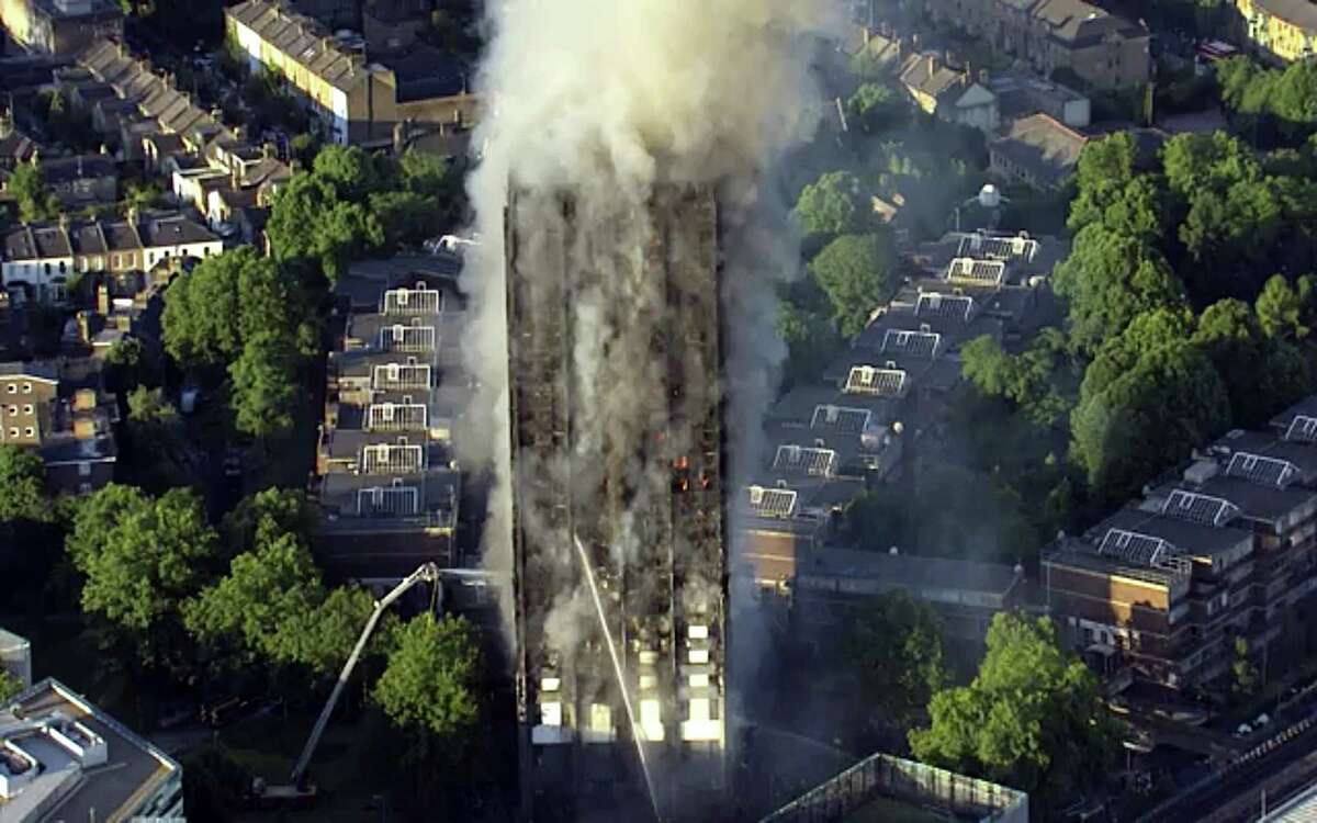 In this photo taken from aerial video, smoke rises from a high-rise apartment building on fire in London on June 14, 2017. A massive fire raced through the 27-story high-rise apartment building in west London early Wednesday, sending at least 30 people to hospitals, emergency officials said.