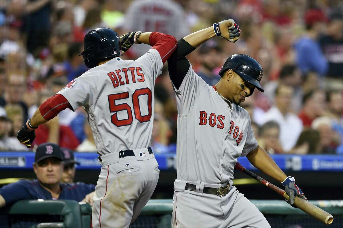 Boston Red Sox's Mookie Betts (50) celebrates with Xander Bogaerts after Betts hit a solo home run off Philadelphia Phillies' Jeremy Hellickson during the fourth inning Wednesday. The Red Sox won 7-3.