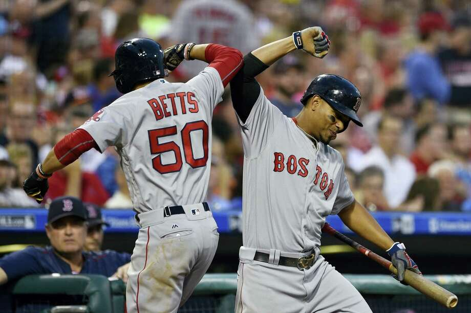 Boston Red Sox's Mookie Betts (50) celebrates with Xander Bogaerts after Betts hit a solo home run off Philadelphia Phillies' Jeremy Hellickson during the fourth inning Wednesday. The Red Sox won 7-3. Photo: DERIK HAMILTON — THE ASSOCIATED PRESS  / FR170553 AP