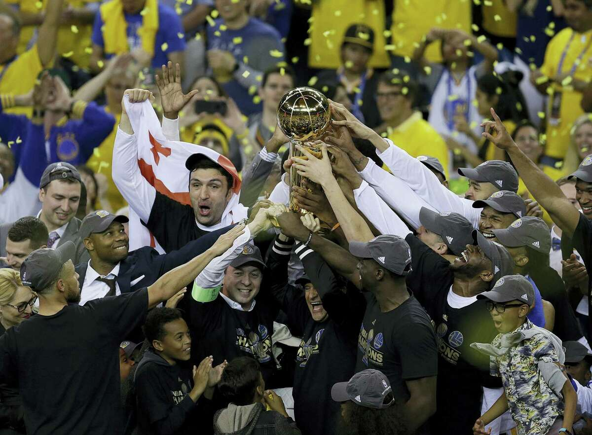 Golden State Warriors players, coaches and owners hold up the Larry O'Brien NBA Championship Trophy after Game 5 of basketball's NBA Finals between the Warriors and the Cleveland Cavaliers in Oakland, Calif. on June 12, 2017. The Warriors won 129-120 to win the NBA championship.