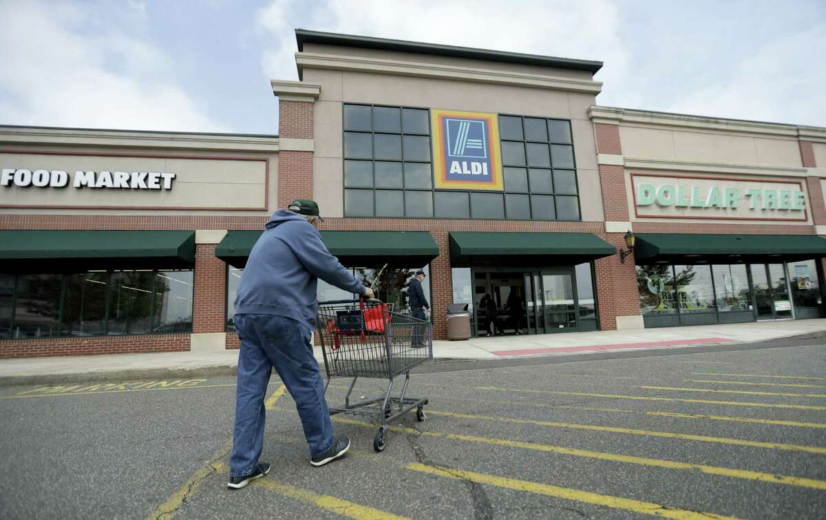 In this May 31, 2017 photo, a customer approaches the entrance of an Aldi food market, in East Rutherford, N.J. Discounter Aldi, one of the no-frills European chains that offer low prices but far fewer options, and mostly its own brands, is putting the pressure on traditional grocers. Aldi expects to have 2,500 U.S. stores by the end of 2022.