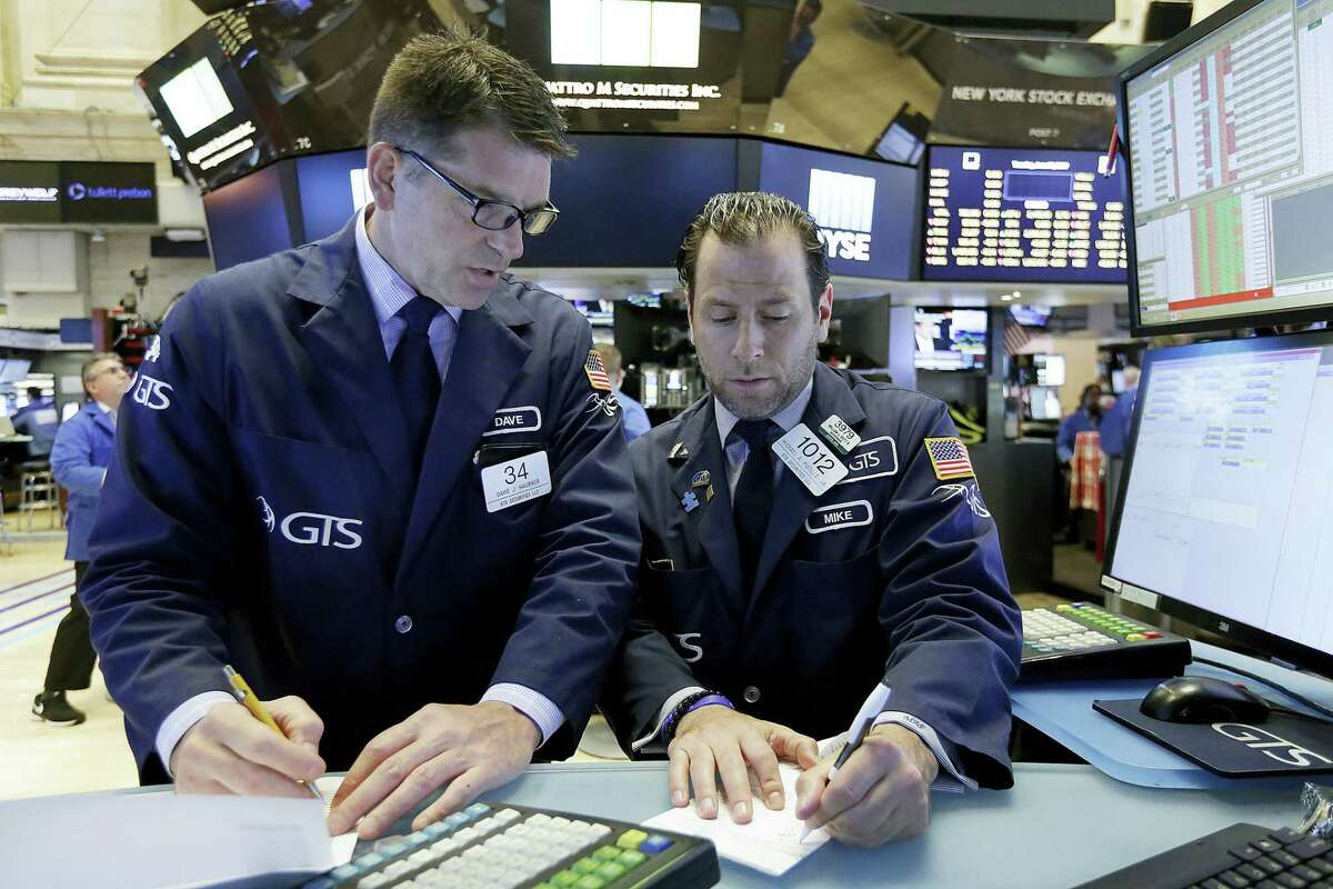 Specialists David Haubner, left, and Michael Pistillo work on the floor of the New York Stock Exchange Tuesday.