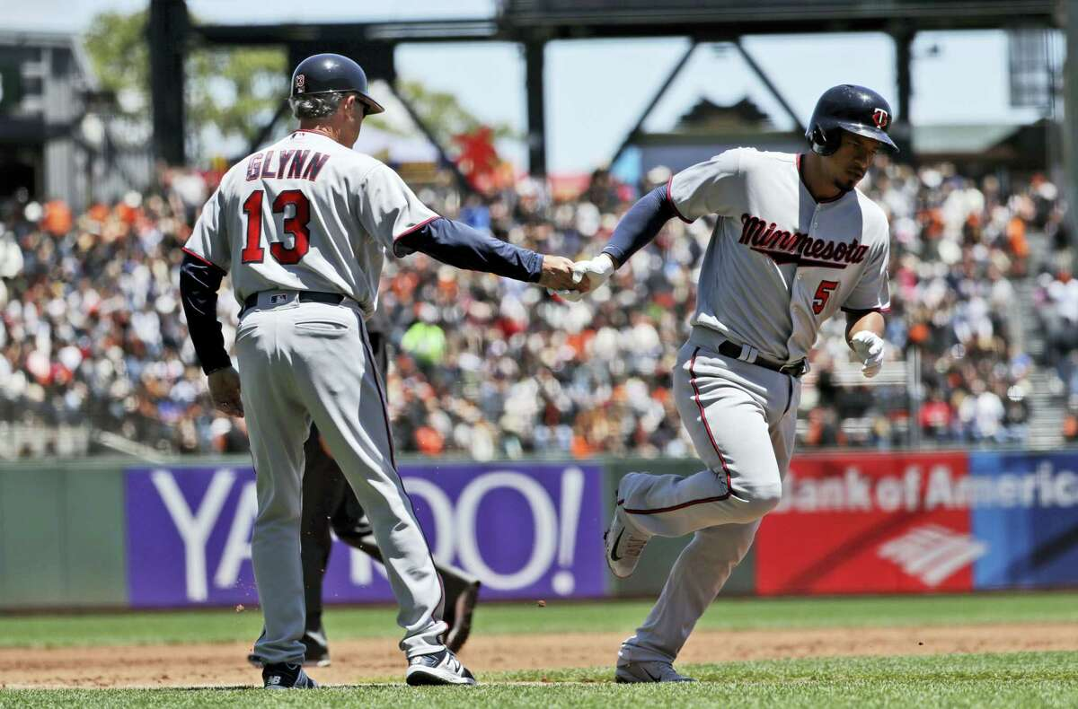 Minnesota Twins' Eduardo Escobar, right, shakes hands with third base coach Gene Glynn (13) after hitting a solo home run against the San Francisco Giants during the second inning of a baseball game on June 11, 2017 in San Francisco.