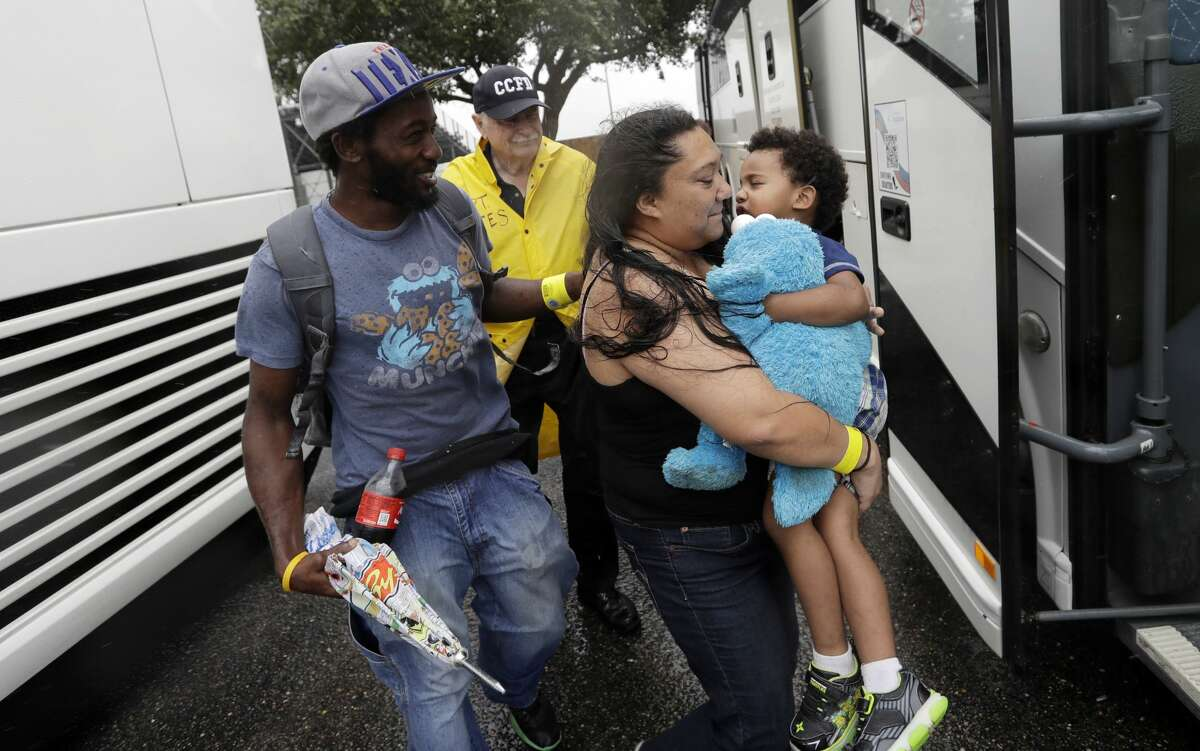 A family is helped to a bus as they are evacuated as the outer bands of Hurricane Harvey begin to make landfall, Friday, Aug. 25, 2017, in Corpus Christi, Texas.