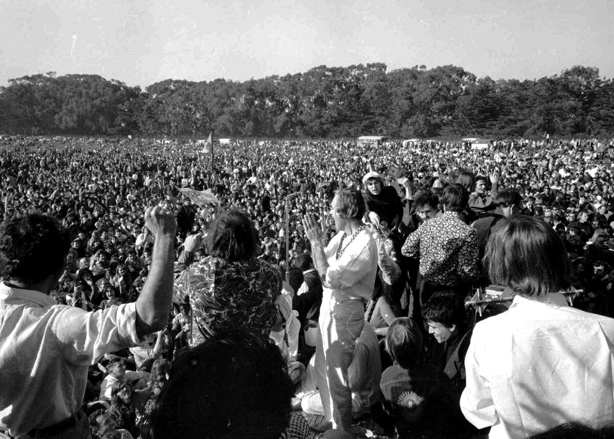 """ADVANCE FOR USE TUESDAY, JUNE 13, 2017 AND THEREAFTER-FILE - In this Jan. 15, 1967 file photo, Timothy Leary, center, leads thousands in a song at the """"Human Be-In"""" on the Golden Gate Park Polo Fields in San Francisco. Dennis McNally, who has curated an exhibit at the California Historical Society, says the national media paid little attention to San Francisco's psychedelic community until January 1967, when poets and bands joined forces for the """"Human Be-In,"""" which unexpectedly drew about 50,000 people. Leary stood on stage and delivered his famous mantra: """"Turn on. Tune In. Drop out."""" (AP Photo)"""