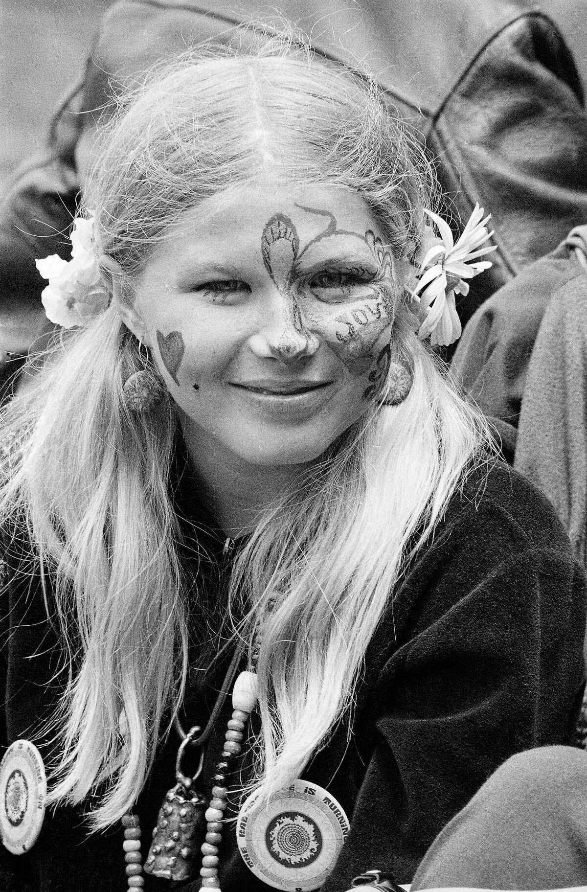 ADVANCE FOR USE TUESDAY, JUNE 13, 2017 AND THEREAFTER-FILE - In this Thursday, June 21, 1967 file photo, Judy Smith, wearing face paint and flowers in her hair, smiles as she and others gather at Golden Gate Park in San Francisco. Fifty years ago, throngs of American youth descended on San Francisco to join a cultural revolution. (AP Photo/Robert W. Klein, File)