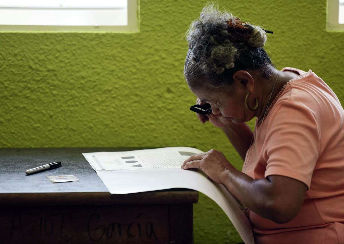 Puerto Rican resident Maria Quinones looks carefully at her ballot with a magnifying glass before voting during the fifth referendum on the island's status, in San Juan, Puerto Rico, Sunday, June 11, 2017. The U.S. Congress ultimately has to approve the outcome of Sunday's referendum that offers voters three choices: statehood, free association/independence or current territorial status. (AP Photo/Carlos Giusti)