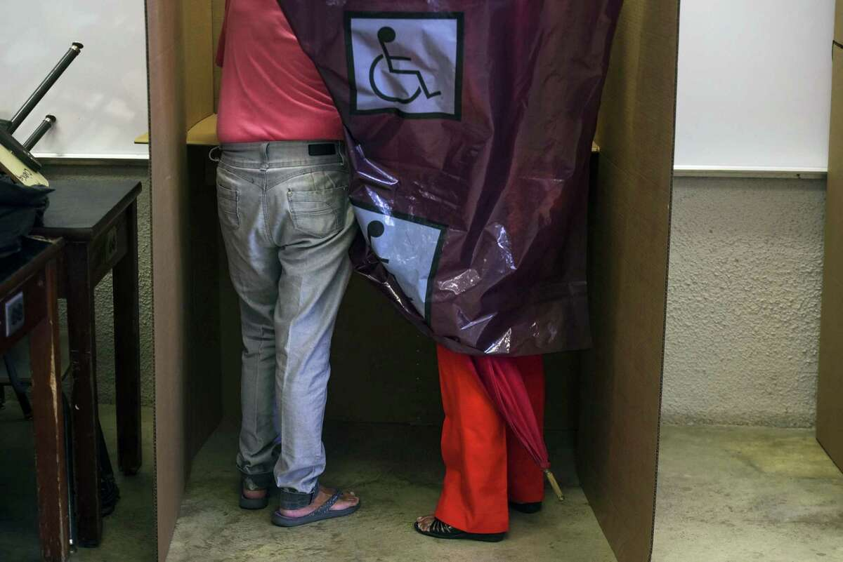 Puerto Rican citizens exercise their vote during the fifth referendum on the island's status, in San Juan, Puerto Rico, Sunday, June 11, 2017. The U.S. Congress ultimately has to approve the outcome of Sunday's referendum that offers voters three choices: statehood, free association/independence or current territorial status. (AP Photo/Carlos Giusti)
