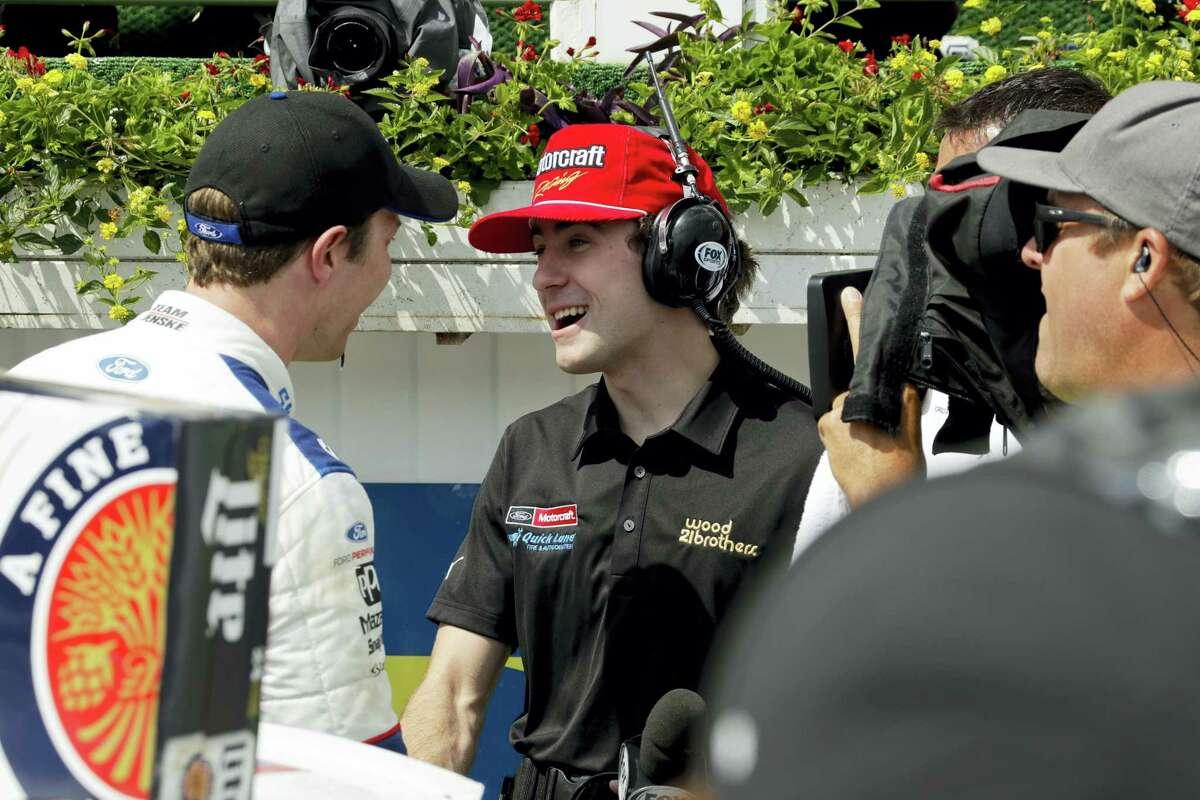 Driver Ryan Blaney, center, interviews Brad Keselowski in victory lane after Keselowski won the NASCAR Xfinity Series race Saturday in Long Pond, Pa.