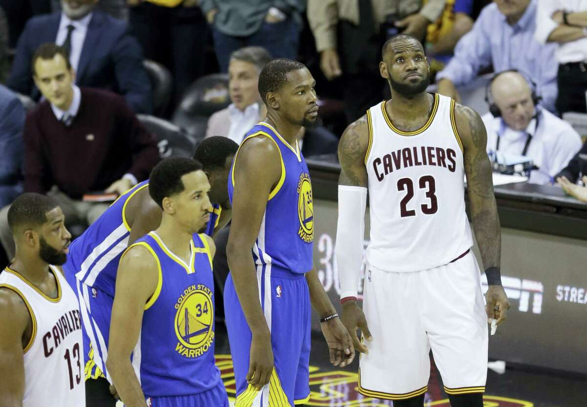 The Warriors' Kevin Durant (35) and the Cavaliers' LeBron James wait to resume play during Game 4 of the NBA Finals in Cleveland on Friday.