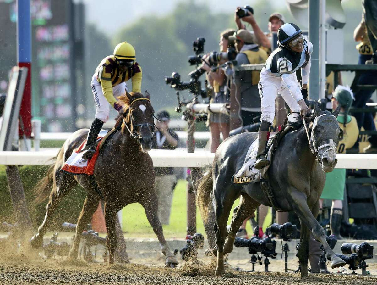 Jose Ortiz celebrates after riding Tapwrit to victory in the 149th running of the Belmont Stakes Saturday in Elmont, N.Y. Irish War Cry, ridden by Rajiv Maragh, is at left.