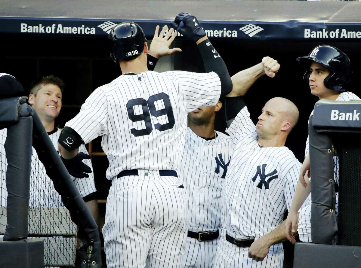 Aaron Judge (99) celebrates with teammates after hitting a home run in the first inning Saturday.