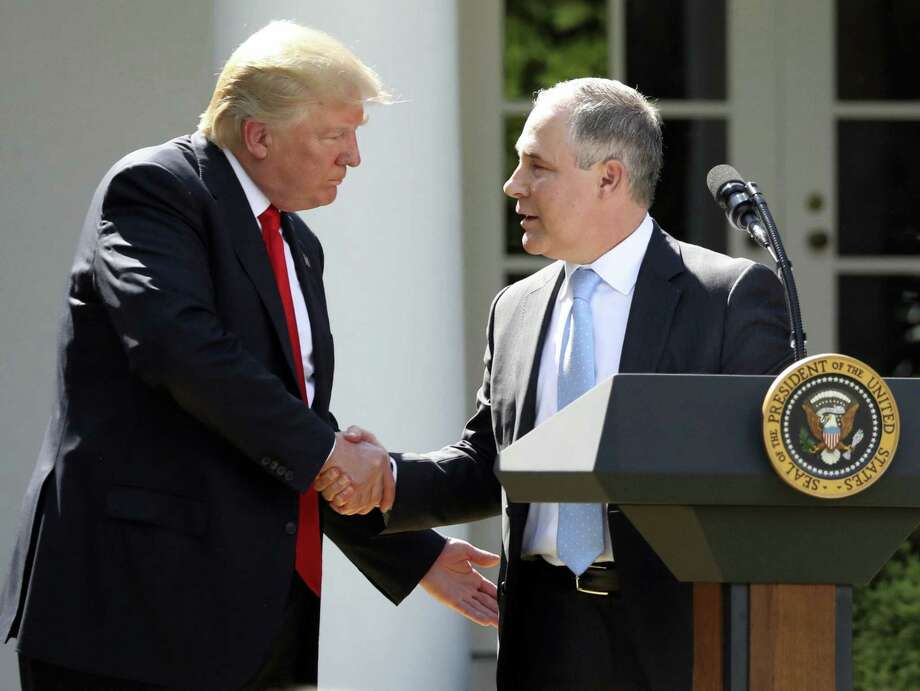 In this June 1, 2017 file photo, President Donald Trump shakes hands with EPA Administrator Scott Pruitt after speaking about the US role in the Paris climate change accord in the Rose Garden of the White House in Washington. Trump's recent decision to pull the United States from the international climate deal reached in Paris was but the latest in a rapid-fire series of moves that would weaken or dismantle federal initiatives to reduce carbon emissions, which scientists say are heating the planet to levels that could have disastrous consequences. Photo: Andrew Harnik/AP Photo, File  / Copyright 2017 The Associated Press. All rights reserved.